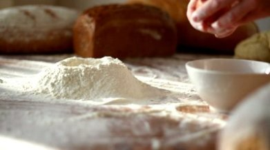 stock-footage-baker-adding-egg-to-flour-on-table-slow-motion
